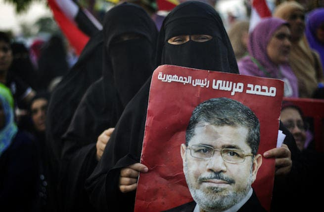 An Egyptian woman holds the portrait of deposed president Mohammed Morsi during a rally in his support outside Rabaa al-Adawiya mosque on July 15, 2013 in Cairo. (Source: AFP/GIANLUIGI GUERCIA)