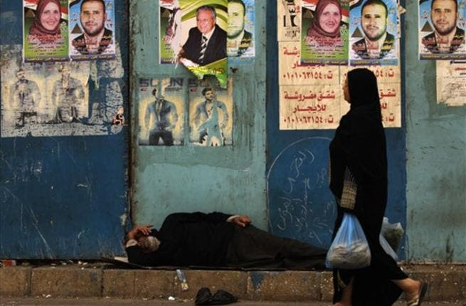 An Egyptian woman walks past a man sleeping next to a wall decorated with election campaign posters next to a polling station in Cairo, as the nation of some 41 million eligible voters goes to the polls.