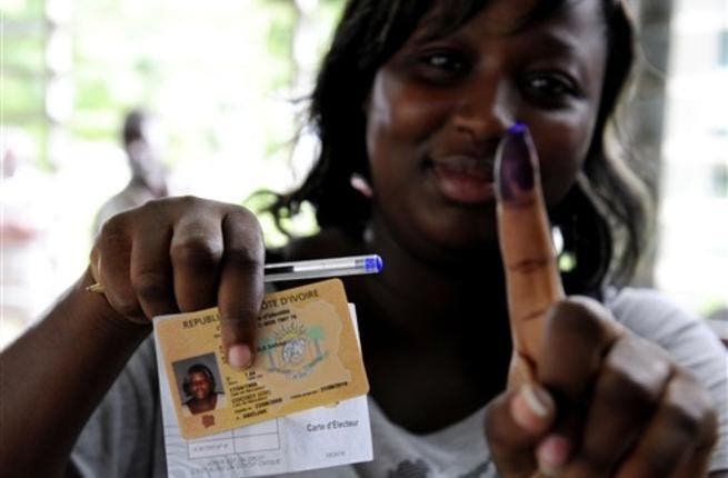 A woman shows documents and a ink-stained finger after voting at a polling station in Abidjan, during the second round of Presidential elections.
