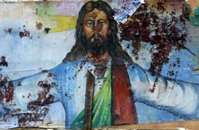 A picture shows a blood-stained image of Jesus Christ outside the Al-Qiddissine church which had been the target of an overnight car bomb attack.