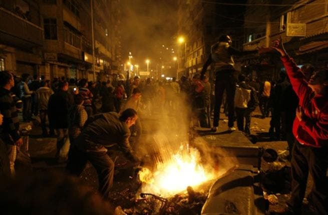 Egyptian Christians burn trash containers during a protest late near the Al-Qiddissine church.