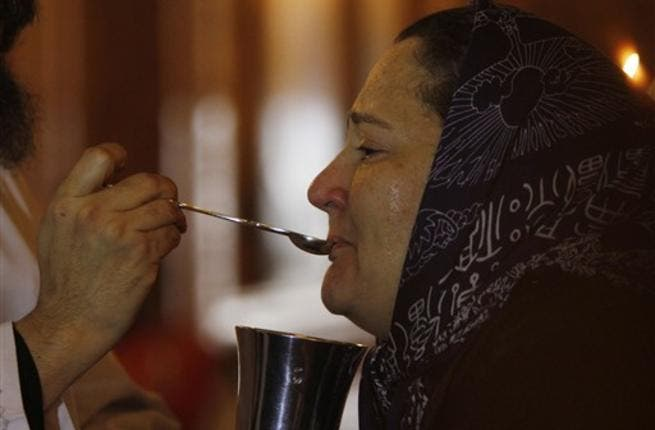 A coptic priest gives a mourning Egyptian woman her communion during Sunday mass on at the Al-Qiddissine church.
