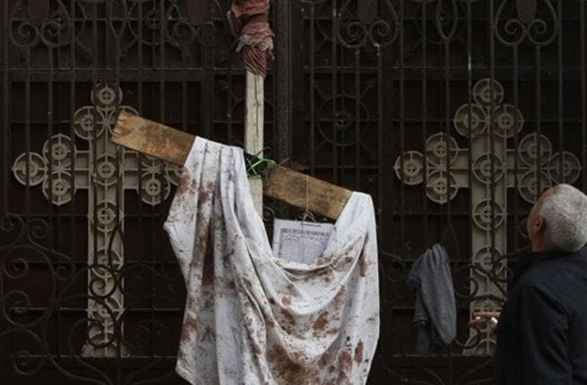 An Egyptian man stands next to a blood-stained peace of cloth hung outside the Al-Qiddisine church in the Mediterranean port city of Alexandria.