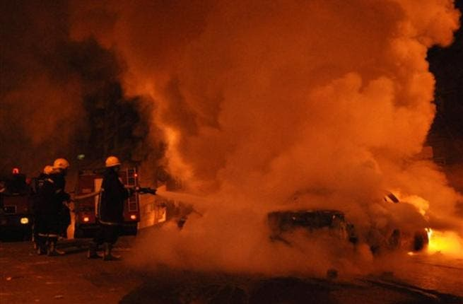 Egyptian firefighters extinguish flames from a vehicle that caught fire following a car bomb attack outside the Al-Qiddissine church.