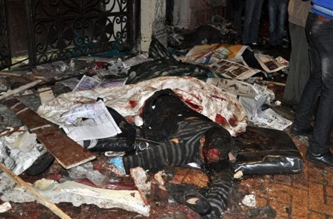 The body of an Egyptian Coptic man is seen on the ground following a car bomb attack outside the Al-Qiddissine church.