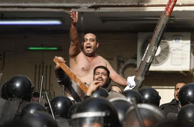 Egyptian Christians face riot police during confrontations outside the Al-Qiddissine church.