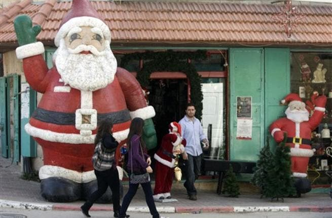 Palestinian women walk past a giant Santa Claus in the biblical West Bank town of Bethlehem, as the town prepares for scores of Christian pilgrims gathering in the traditional birthplace of Jesus Christ to celebrate Christmas.