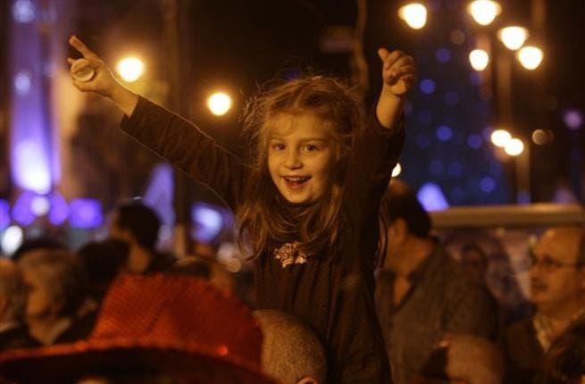 A child enjoys listening to a choir during Christmas Eve celebrations, in the Ashrafiyeh neighborhood of east Beirut.