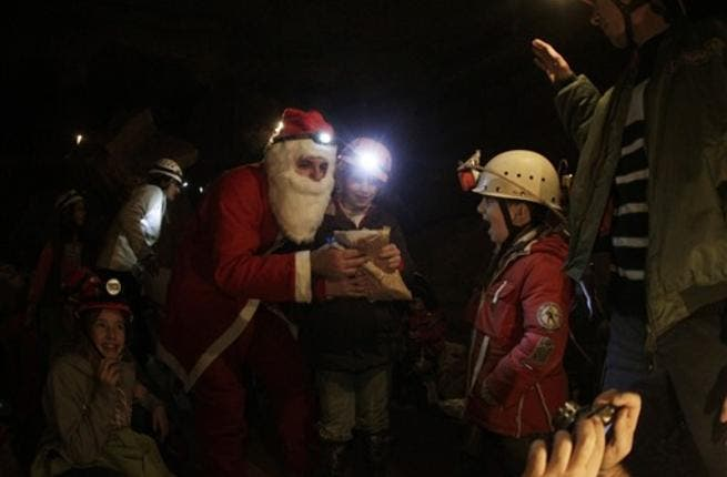 A Lebanese caver from the(ALES) disguised as Santa Claus, distributes gifts to children of the Association members and their comrades as the cavers celebrate with them Christmas inside a cave in the village of Rweiss nearly at 2000 meters above sea level in the Lebanese mountains north of Beirut.