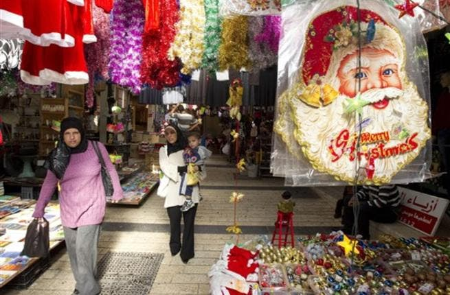 Arab-Israeli women walk past stalls selling Christmas decorations at a market in the Arab-Israeli town of Nazareth.