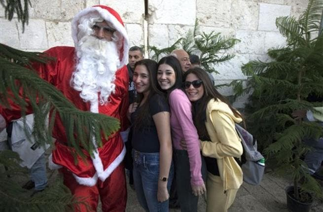 Israeli women pose for a picture with a Palestinian man dressed as Santa Claus standing between Christmas trees at a municipality distribution point at Jaffa Gate in Jerusalem's old city, ahead of Christmas celebrations.