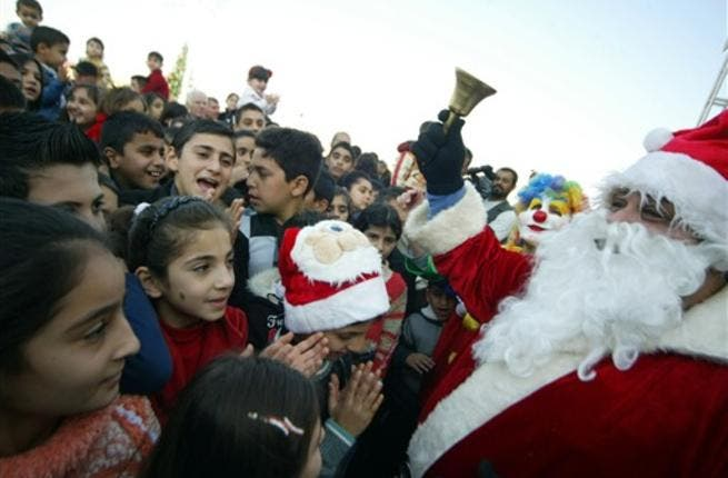 Mainly Iraqi Kurd children gather to greet Santa Claus in the northern Iraqi city of Arbil on Christmas eve.