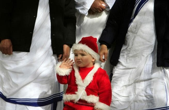 A Palestinian Christian boy wearing a Santa Claus costume waves during a ceremony ahead of Christmas attended by the head of the Roman Catholic Church in the Holy Land, the Latin Patriarch of Jerusalem Fuad Twal, outside the Latin Catholic Church in Gaza City.