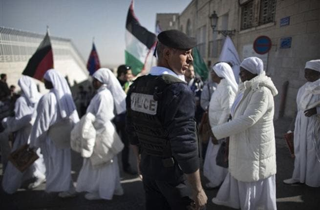 A Palestinian policeman stands guard as Nigerian worshippers cross a street near the Church of the Nativity in the Biblical West Bank city of Bethlehem, believed to be the birthplace of Jesus Christ, in the West Bank town of Bethlehem, as the Holy Land prepares to mark Christmas.