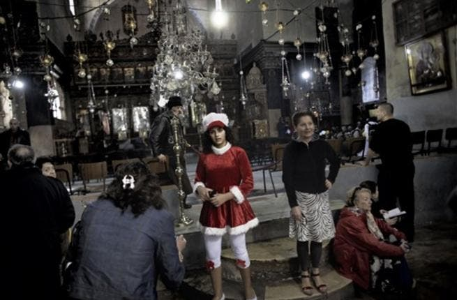 A Palestinian girl dressed in a Santa Claus attire poses alongside other worshippers inside the Church of the Nativity in the West Bank city of Bethlehem, as Christian flock to the what they believe is the birth place of Jesus Christ to celebrate his birth during Christmas mass.