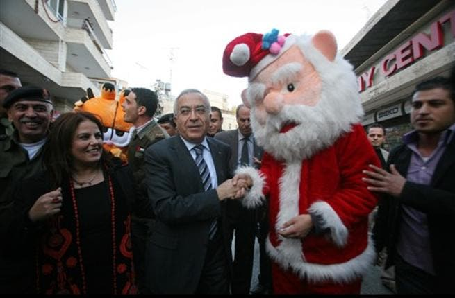 Palestinian prime minister Salam Fayyad (C) shakes hands with a man dressed as Santa Claus as he takes part in the 3rd annual march for unity and peace marking Christmas in the biblical West Bank town of Bethlehem.