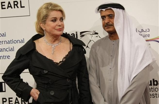 French actress Catherine Deneuve poses for a photograph with the Chairman of the DIFF Abdulhamid Juma.