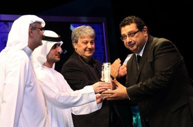 Sheikh Said bin Mohammed bin Rashed al-Maktoum (2nd L) hands the best actor award to Egypt's Maged al-Kidwany.