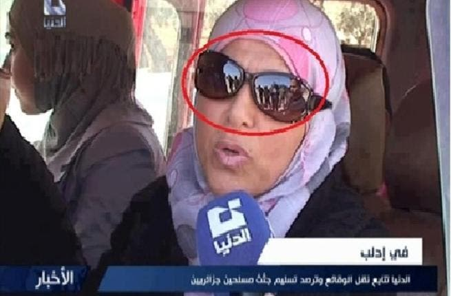 The Shabiha in the mirror: This woman interviewed by Dounia TV told them there were no problems for her country but her sunglasses told a different story - the infamous pro-Assad 'Shabiha' thugs were seen in the background.