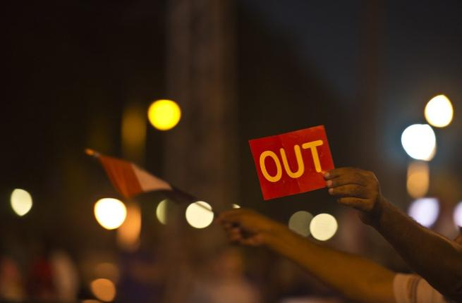 An Egyptian man holds up a red card against the country's Islamist President in front of the presidential palace in Cairo (AFP)