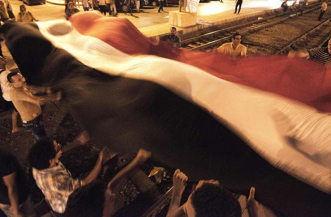 Opponents of the Egyptian president wave a giant national flag outside the presidential palace (AFP)