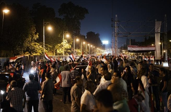 Hundreds of Egyptian protesters wave national flags and shout slogans against President Mohammed Morsi outside the presidential palace (AFP)