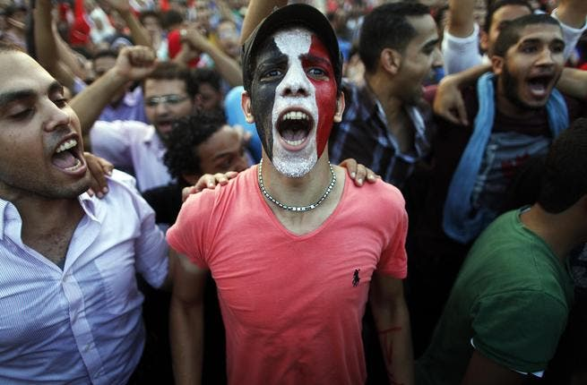 Egyptians shout slogans against President Mohamed Morsi and the Muslim Brotherhood as hundreds of thousands of Egyptian demonstrators gather at the presidential palace during a protest calling for the ouster of Morsi on July 1, 2013 in Cairo.