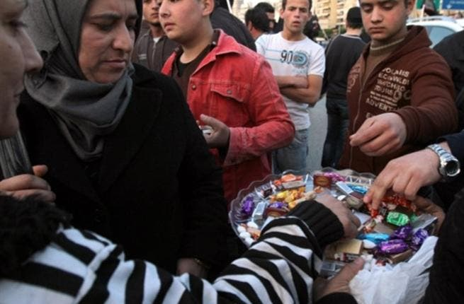 In Lebanon, sweets are distributed outside the embassy in Beirut to celebrate the sweet victory marked by the resignation of Egypt's Hosni Mubarak, President of the Republic of Egypt, Friday, February 11, 2011.