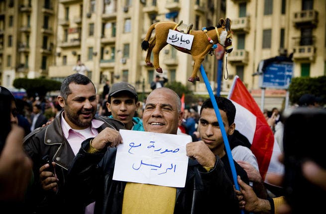 An Egyptian man is holding a placard that reads
