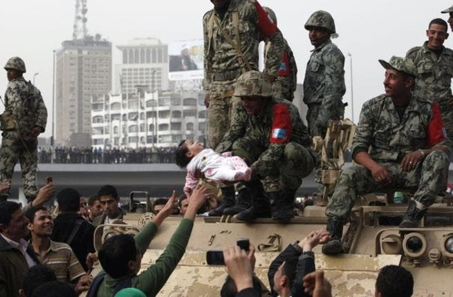 An Egyptian soldier raises an infant of the Protest in testimony to the good feeling between the Military and the People this last week.
