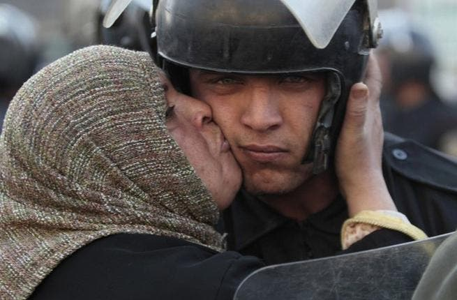 Early days in this marathon display of people power: An Egyptian woman guilts the patrolman into re-considering his stance,through a message of admonition in a firm kiss to a befuddled riot-policeman:You are of us and from us,says this charged kiss.