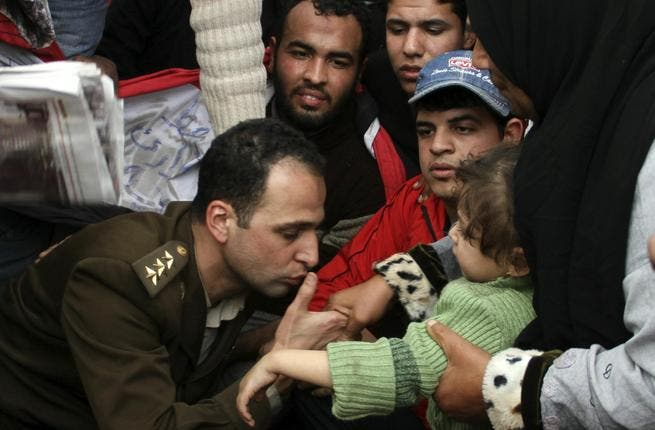 An Egyptian officer shows his position of solidarity with his people by a kiss to a child in the arms of its mother.