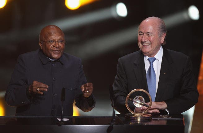 Archbishop Desmond Tutu (L) of South Africa receives the Presidential award from Sepp Blatter (R) President of FIFA.