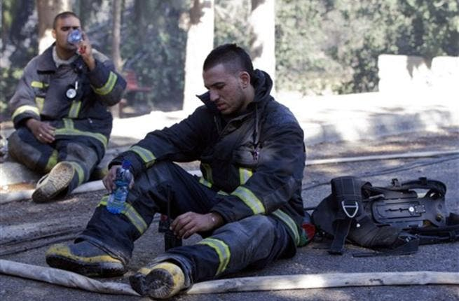 Israeli firefighters take a break after dousing flames in the village of Ein Hod.