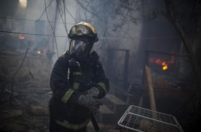 An Israeli firefighter stands at the site of a burning house in the village of Ein Hod, as the massive fire ripping through northern Israel was still incinerating swathes of land, with little sign that Israeli and foreign firefighters were winning the battle to contain it.