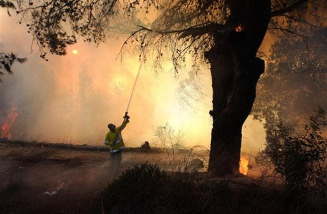 Israeli firefighters try to extinguish fire in the Carmel Forest near the northern city of Haifa, as global help poured in to battle the biggest inferno in the country history