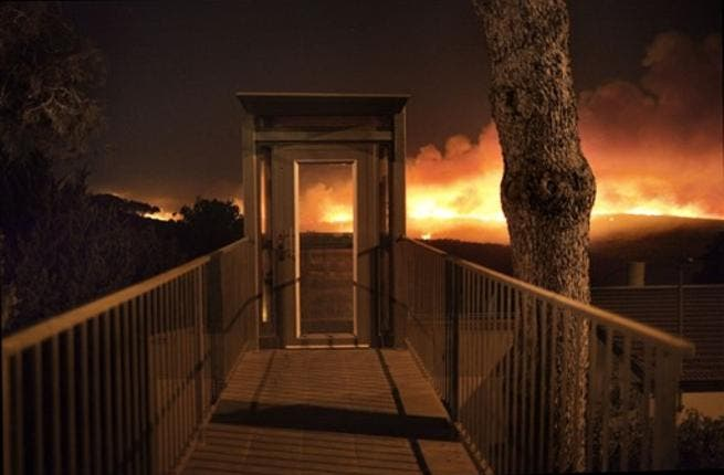 A forest fire rages out of control in front of a residential house  in the hills above the coastal Israeli city of  Haifa.