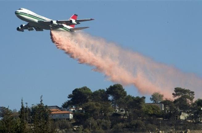 US Evergreen 747 supertanker sprays over an area in Ein Hod in the Carmel Forest in the outskirts of Haifa, as dozens of firefighting planes from around the world battled the blaze, which has killed 41 people so far.