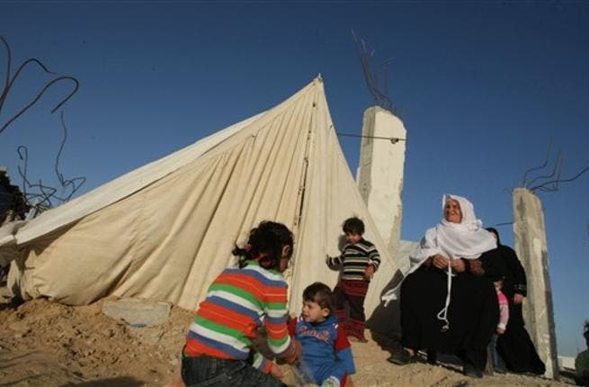 Members of a displaced Palestinian family sit outside their tent.