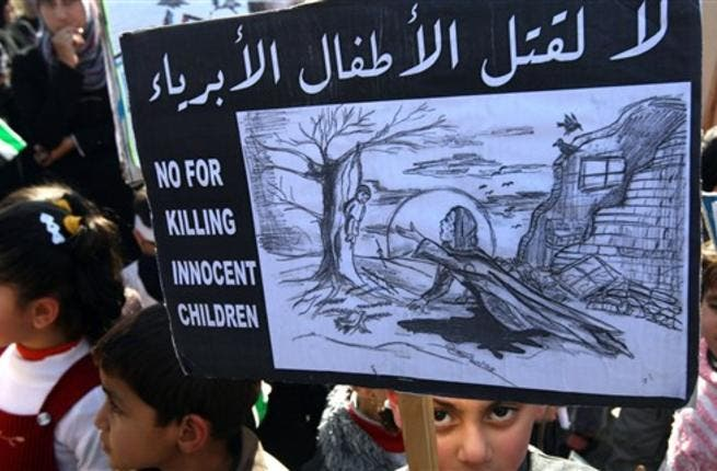 No for killing innocent children sign, held by Palestinian children who took a part in protesting against the invasion of Gaza two years ago.
