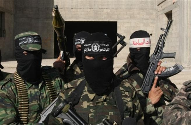 Armed Palestinians are seen following a press conference.