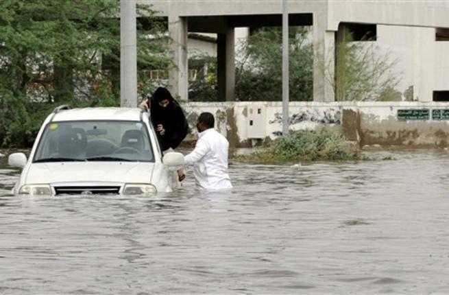 A Saudi man and a woman leave their car after it got stuck in a flooded street following heavy rain in the Red Sea port city of Jeddah.