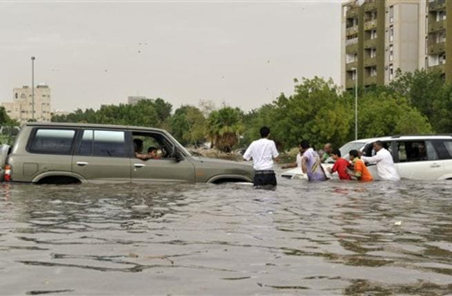 Saudi men are trying to push a car stuck in a flooded street.