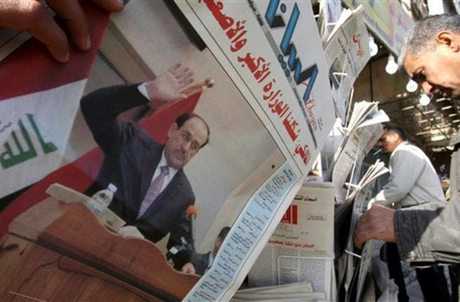 Iraqis pick up newspapers featuring a front-page story on the country's new cabinet at a kiosk in Baghdad, a day after the Iraqi parliament gave Prime Minister Nuri al-Maliki's government a vote of confidence and adopted a 43-point program.