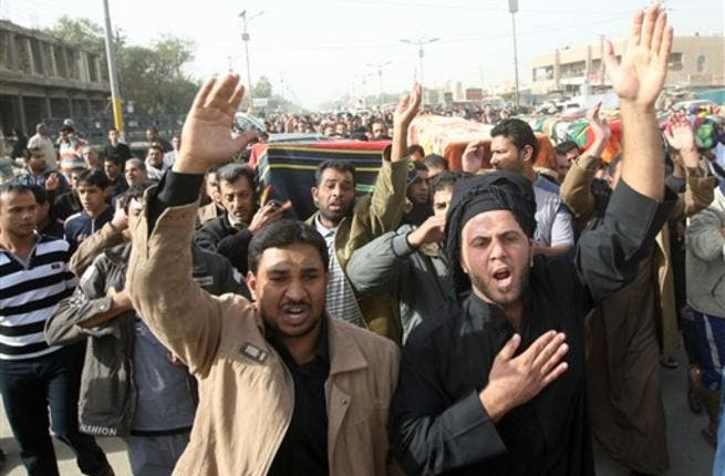 Iraqi Shiite Muslims carry the coffins of people killed in a bomb blast that targeted a convoy of pilgrims in the Ghazaliyah district of Baghdad.