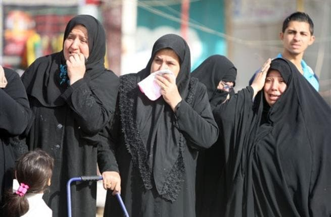 Iraqi Shiite Muslim women grieve as they watch the funeral procession of people killed in a bomb blast that targeted a convoy of pilgrims in the Ghazaliyah district of Baghdad as Shiite Muslims prepare to mark the religious event of Ashura on December 17.