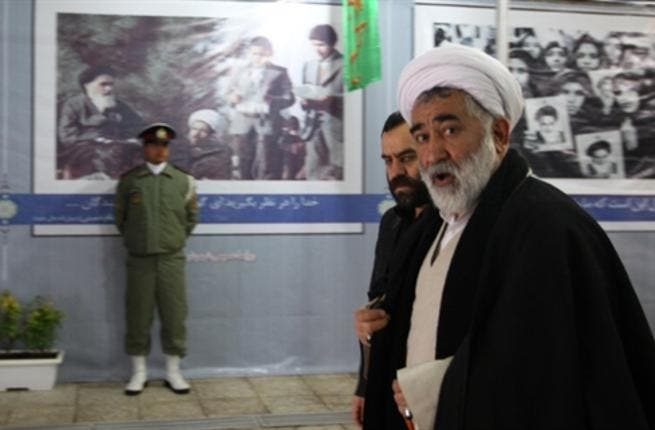 Clerics walk past posters showing the late founder of the Islamic Revolution Ayatollah Ruhollah Khomeini, outside Khomeini's mausoleum as they arrive to attend the ceremony.