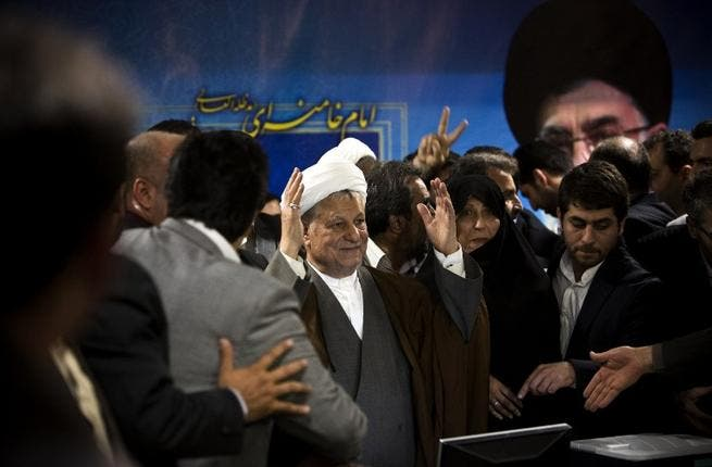 Former Iranian president Akbar Hashemi Rafsanjani (C) arrives with his daughter Fatemeh (C-R) to register his candidacy for the upcoming presidential election at the interior ministry in Tehran on May 11, 2013. (AFP)
