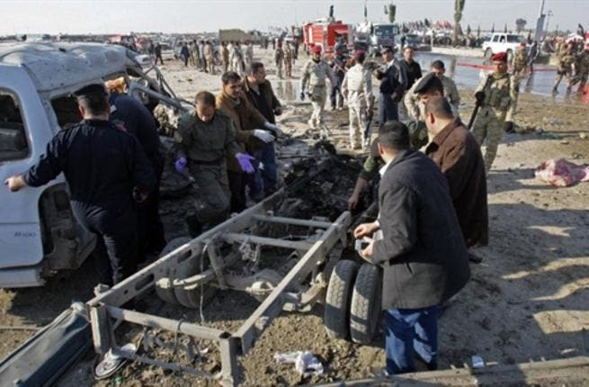 Members of Iraq security forces gather on the site of an explosion in Karbala.
