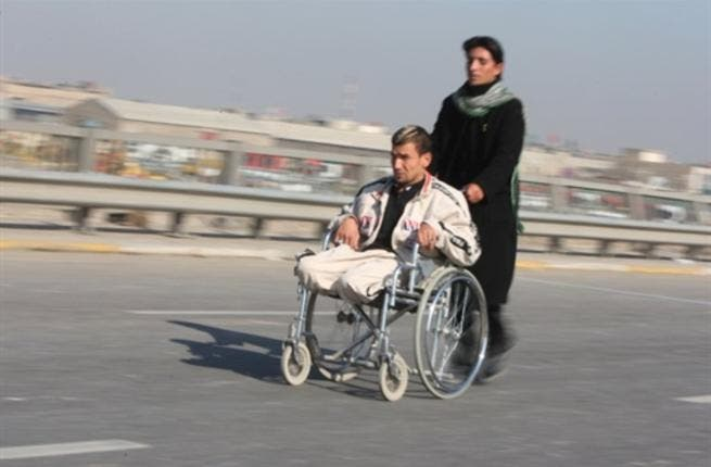 A handicapped Shiite pilgrim is pushed on a wheelchair on a highway linking Baghdad to Karbala, 120 kms south of the capital.